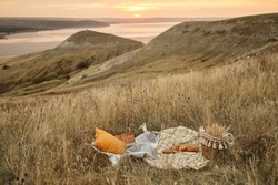 Romantic picnic in nature with panoramic background. The beauty of the setting sun, fresh fruits. Romantic dinner outdoors. Picnic on the hill at sunset with river background.