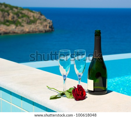 Romantic picnic near infinity pool in luxury mediterranean resort. Champagne and rose. Greece