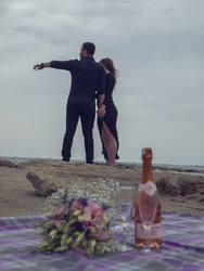 Romantic picnic of loving couple with seaside and mountain view. expensive bottle of white wine, blank label and two glasses