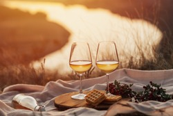 Romantic picnic on the mountain with river and sunset on background. Bottle of wine, glasses and dessert.