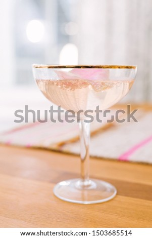 Romantic pink bubbly sparkling cocktail made with champagne, vodka, and rose water, shaken with ice, served in gold rimmed coupe glass, garnished with rose petal. Photo stock ©