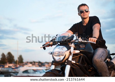 Romantic portrait handsome biker man in sunglasses sits on a bike on a sunset near lake and yacht club. copy space left