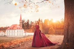 Romantic portrait of a young girl in a long red dress standing in the wind against the background of an ancient castle and autumn nature