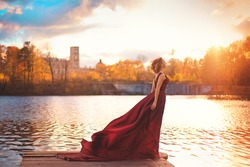 Romantic portrait of a young girl in a long red dress standing near the columns of an old manor house on the background of autumn nature