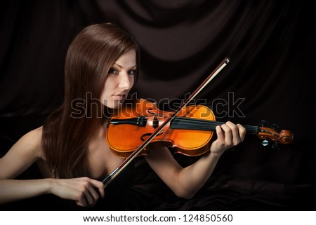Romantic portrait of beautiful woman with violin, dark background