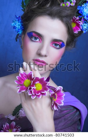 Romantic portrait of charming woman with artistic visage and flowers in her hair.