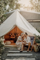 Romantic portrait of couple celebrating honeymoon on their holidays and tour in Thailand. Loving wife and husband kiss in background of tent and nature in sunny day.