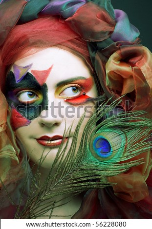 Romantic portrait of woman in creative image with peacock feather