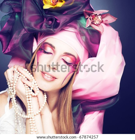 Romantic portrait of young lady with original make-up  in pink turban with orchids