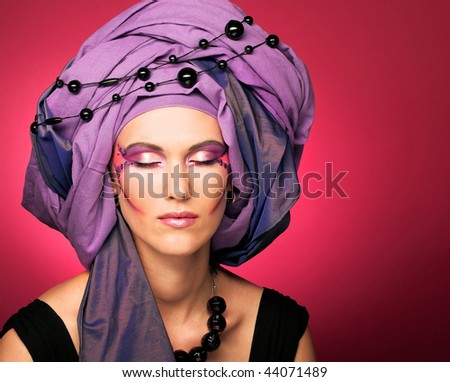 Romantic portrait of young woman in violet turban and black beads
