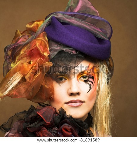Romantic portrait of young woman with bright creative make-up in fantastic hat #81891589