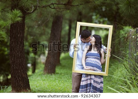 Romantic pregnant couple kissing under pine tree while holding a frame