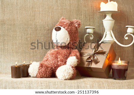 Romantic present. Teddy bear toy with gift box and candles on sack/burlap background. Filtered image. Indoors still-life.