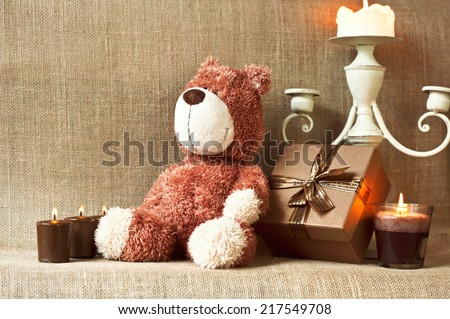 Romantic present. Teddy bear toy with gift box and candles on sack/burlap background with filter. Indoors still-life.