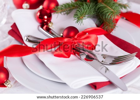 Romantic red Christmas table setting with white plates, red and white linen and silverware tied with a red ribbon and bow decorated with red Xmas baubles and evergreen natural pine foliage