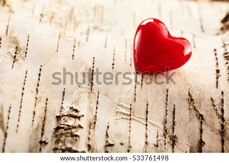 Romantic red Valentines heart symbolising love and affection in the corner over a background of natural textured wood bark with copy space for your message to a loved one