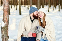 Romantic relationship and winter holiday vacation concept. Happy smiling couple under warm plaid with cups of hot drinks hugging and kissing outdoors in winter forest. Romantic couple in love feeling