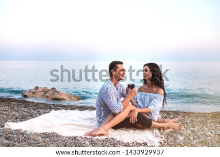 Romantic Romantic couple sitting with wineglasses at seaside at sunset. Romantic concept. #1433929937