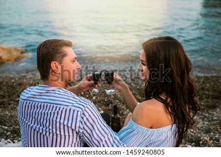 Romantic Romantic couple sitting with wineglasses at seaside at sunset. Romantic concept.