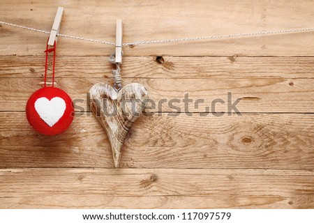 Romantic rustic Valentines greeting background with handcrafted wooden heart and colourful textile heart bauble hanging on a line from pegs over natural wooden boards
