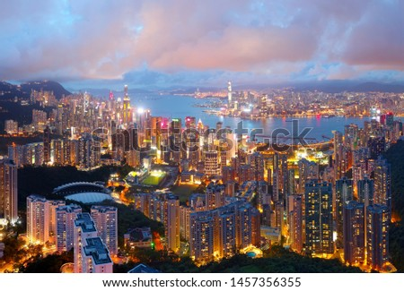 Romantic scene of Hong Kong at nightfall, with residential towers on Mid-Levels hillside in Hong Kong Island & colorful city lights of skyscrapers by Victoria Harbour dazzling under moody twilight sky