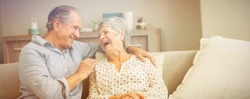 Romantic senior couple laughing while sitting on sofa at home