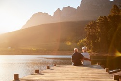 Romantic Senior Couple Sitting On Wooden Jetty By Lake