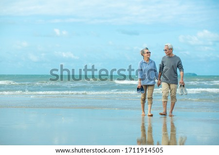 Romantic senior couple while walking hand in hands and talking together at beach. Retirement age concept and love.