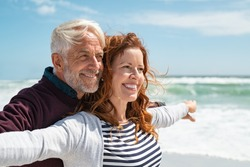 Romantic senior couple with outstretched arms enjoying vacation. Old husband embracing from behind beautiful wife at sea. Happy smiling mature couple carefree: future, imagination and contemplation.
