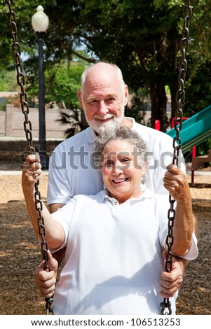 Romantic senior husband pushing his lovely wife in a swing on a playground.