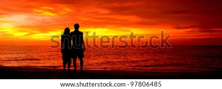 Romantic silhouette of a loving couple on honeymoon looking at a beautiful red sky sunset in Maldives, Indian Ocean.