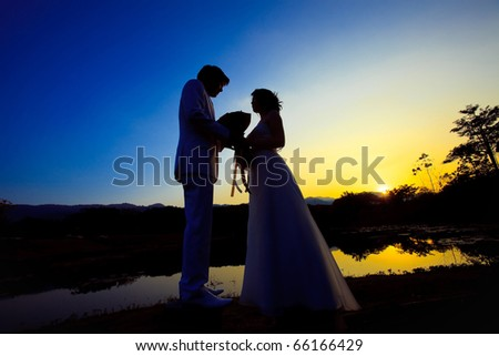 romantic silhouette picture of bride and groom after sunset
