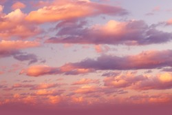 Romantic sky background, beautiful fluffy pink clouds, amazing view on the dramatic sunset sky, natural textured wallpaper, vanilla sky