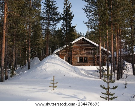 Romantic snow covered chalet in a forest of pine trees in a holiday resort in Lapland, Finland. Perfect for the christmas holidays.