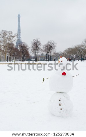 Romantic snowman near the Eiffel tower in Paris, France