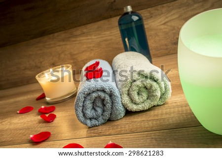 Romantic Spa Still Life Concept for a Couple with Two Rolled Towels, Lit Candle, Bottle of Massage Oil and Essential Oil Diffuser Surrounded by Red Rose Petals with Wooden Background.