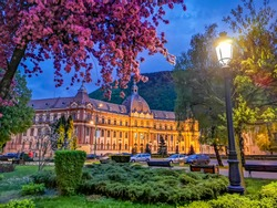 Romantic spring scene in Brasov with lamp and blooming pink tree in front of Town Hall building, Romania