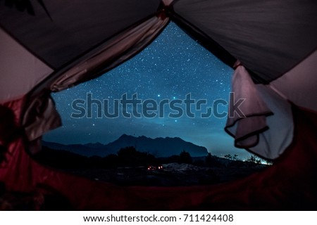 Romantic starry sky night view from inside of tent.  Camp with spectacular starry sky wtih mountain background. #711424408