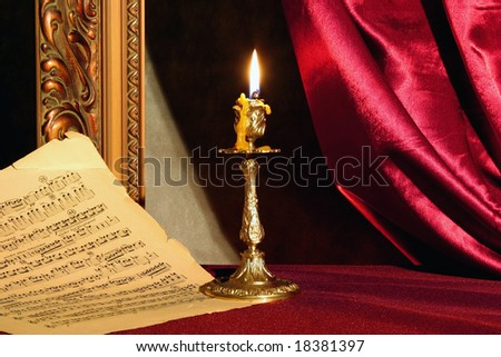 Romantic still-life with burning candle and music sheet.