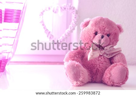 Romantic still life with pink plushy teddy bear in the foreground a pink curtain and heart in the background
