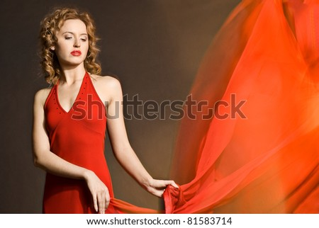 Romantic style photo of beautiful young lady wearing red dress with scarf