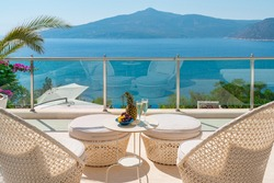 Romantic summer vacation view. Luxury travel balcony with ocean view.  Drinks and fruits on table holiday destination.