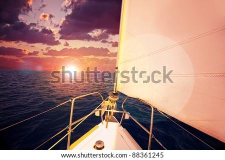 Romantic sunset and sail boat, dramatic sky with purple clouds and sun flare over calm sea, water sport, travel and freedom concept