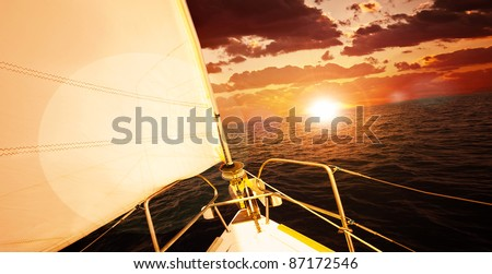 Romantic sunset and sail boat, dramatic sky with red clouds and sun flare over calm sea, water sport, travel and freedom concept
