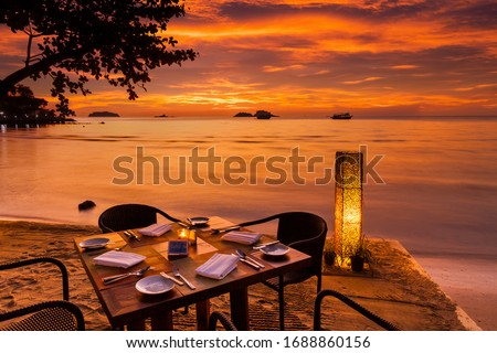 Romantic sunset on the shore of a tropical island. Cafe on the beach. Dinner table