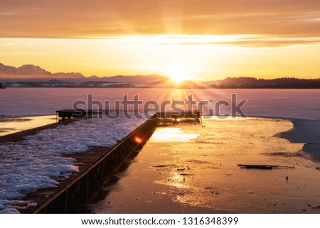 romantic sunset over a frozen lake, with wooden pier, wallersee, austria #1316348399