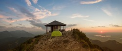 romantic sunset scenery at herzogstand mountain, pavilion and camping tent at the summit. bavarian alps.