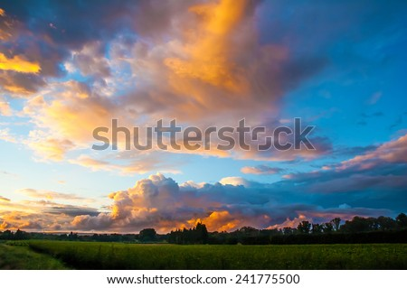 Romantic sunset sky with fluffy clouds.