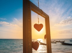 Romantic symbol of hearts in the wooden  frame at the sea background Red heart model at the sandy sea beach with blue sea blurred background. Heart shape framing with sunset on summer beach