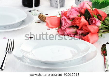 Romantic table setting for two with a bouquet of roses. Shallow depth of field.